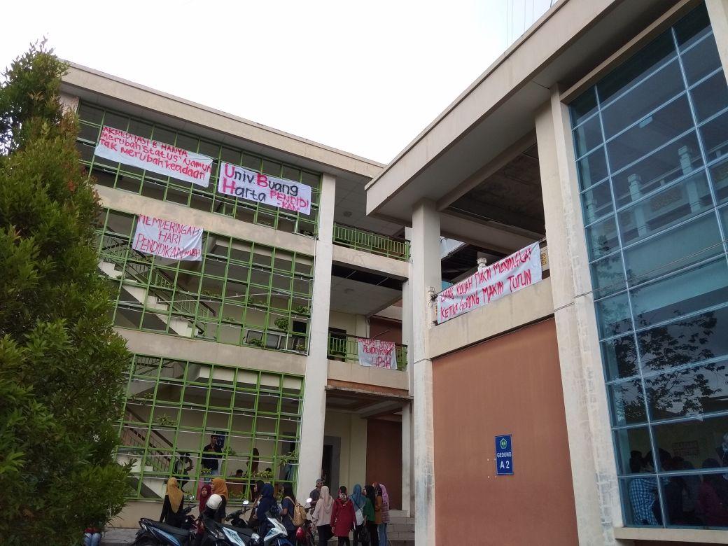 Mahasiswa Fakultas Ekonomi Universitas Bung Hatta, Padang Sumatera Barat memasang spanduk di sejumlah gedung kampus saat peringatan Hardiknas 2018