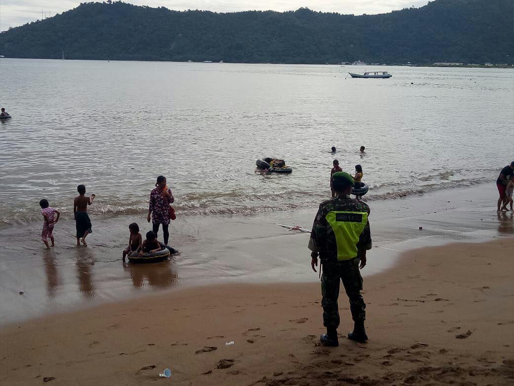 Babinsa Koramil 07/Bungus Kodim 0312/Padang saat melakukan pengamanan di kawasan obyek wisata selama Lebaran 2018 di Padang, Sumatera Barat.