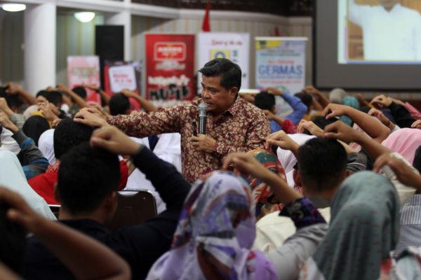 Seorang Instruktur terapi Spritual Emotional Freedom Tehknique, Benii Warlis (empat ke kanan) mencontohkan pada peserta yang mengikuti terapi rokok berhenti massal di kantor gubernuran Sumatera Barat, Padang,