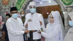 Pasangan pengantin Perinaldi dan Riska Alida yang menikah di Masjid Babussalam Muhammadiyah menerima Sikado